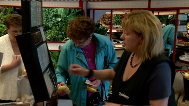 shoppers in wales to be charged for platic carrier bags unidentified location int assistants at greengrocer's checkout putting customer's groceries... - lebensmittelhändler stock-videos und b-roll-filmmaterial
