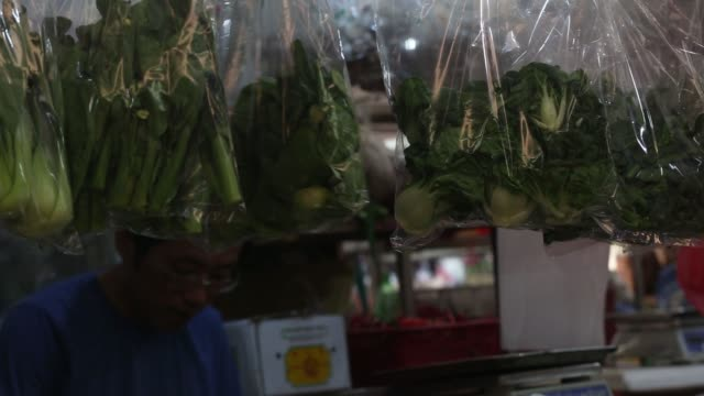 shoppers look at plastic wrapped vegetables hanging at a vegetables stall at a wet market in the tiong bahru area of in singapore, on sunday, june 4... - eingewickelt stock-videos und b-roll-filmmaterial