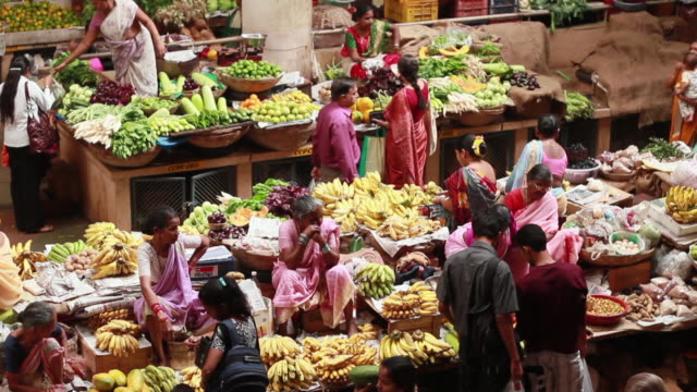 Shoppers look for fruit at a market.