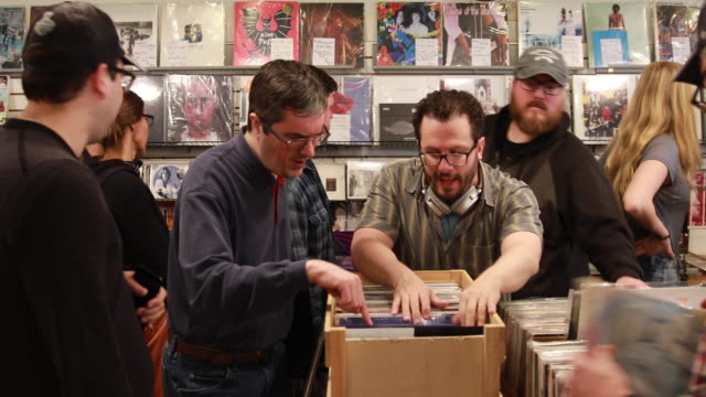 vídeos de stock, filmes e b-roll de shoppers look for rare and limited edition records during record store day saturday april 21 2018 at landlocked music in bloomington indiana buyers... - bloomington indiana