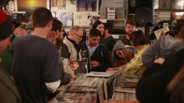 shoppers look for rare new and rereleased recordings on vinyl and cd during the 10th anniversary record store day at landlocked music in bloomington... - compact disc stock videos & royalty-free footage