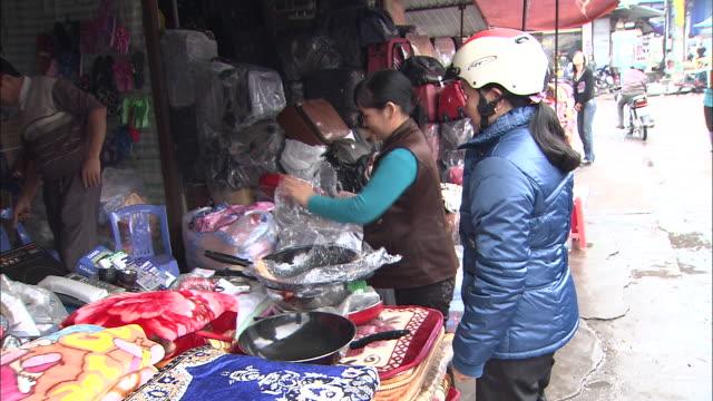 vídeos y material grabado en eventos de stock de shoppers looking at skillets: long shot. - cabello recogido