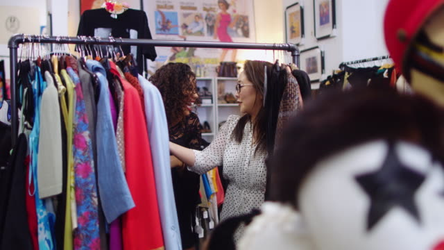 shoppers looking through rack of vintage clothes - mercato delle pulci video stock e b–roll