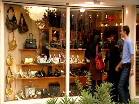 vídeos y material grabado en eventos de stock de shoppers looking through windows and walking through retail district / tehran, iran - formato buzón