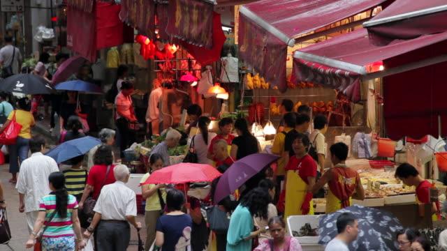 vídeos de stock, filmes e b-roll de shoppers, many with umbrellas, move through a busy market in wan chai. - wan chai