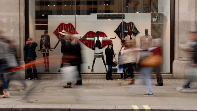 vídeos de stock e filmes b-roll de shoppers move rapidly past a fashion window display on oxford street - mercadoria