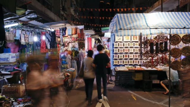 shoppers move through the temple street night market in hong kong. - temple street market stock videos and b-roll footage