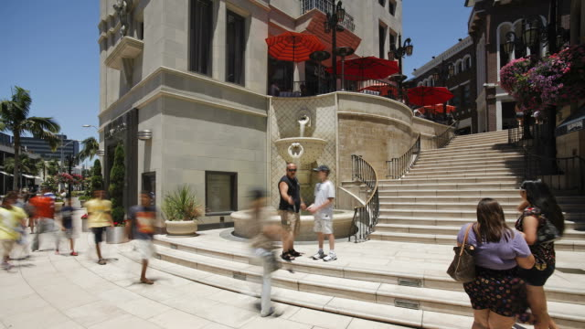 shoppers move up and down stairs on rodeo drive in beverly hills. - ビバリーヒルズ点の映像素材/bロール