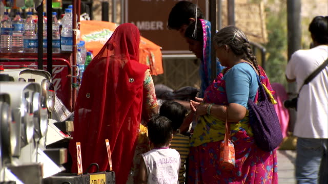 shoppers negotiate with a street vendor. available in hd - two generation family stock videos & royalty-free footage