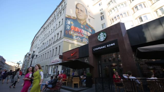 shoppers pass beneath a wall mural depicting russian general georgy zhukov a world war ii soviet hero on arbat street in moscow russia on monday june... - nike designer label stock videos and b-roll footage