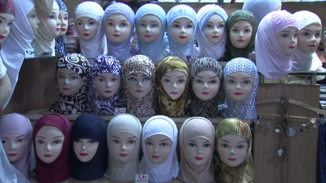 shoppers pass by a booth displaying hijabs on mannequins. - hijab stock videos and b-roll footage