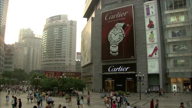 shoppers pass the cartier store in a japanese shopping district. available in hd. - cartier video stock e b–roll