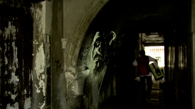 shoppers pass through an arched stone corridor in a venice ghetto. available in hd. - ghetto video stock e b–roll