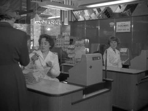 vídeos de stock e filmes b-roll de shoppers pay for their goods at checkouts in a supermarket - vendas