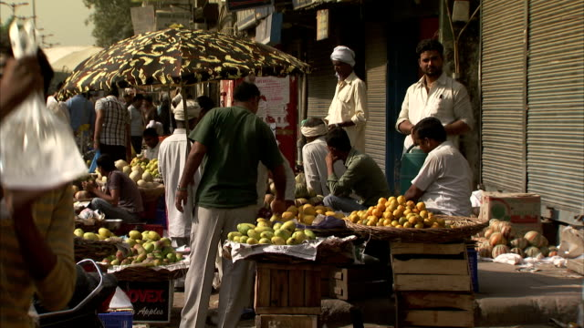 shoppers peruse the selection at a fruit stand. - delhi stock videos & royalty-free footage