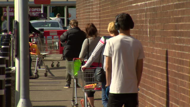 shoppers practicing social distancing while queueing for the supermarket - cart stock videos & royalty-free footage