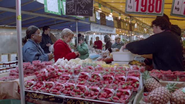 vidéos et rushes de shoppers purchase fruit at a market in paris, france. - fraise