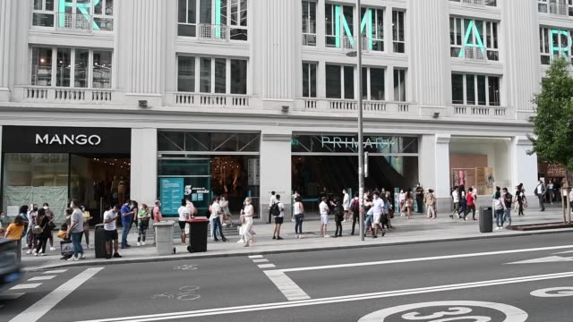 shoppers queue in a line to enter the primark store on june 17, 2020 in madrid, spain. primark reopens to the public after its closure in the middle... - マドリード グランヴィア通り点の映像素材/bロール