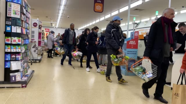 shoppers queuing as the country prepares to practise 'social distancing' as the government advises members of the public to work from home and stay... - social distancing stock videos & royalty-free footage