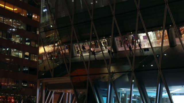 shoppers reflected in modern facade at night - mirror点の映像素材/bロール