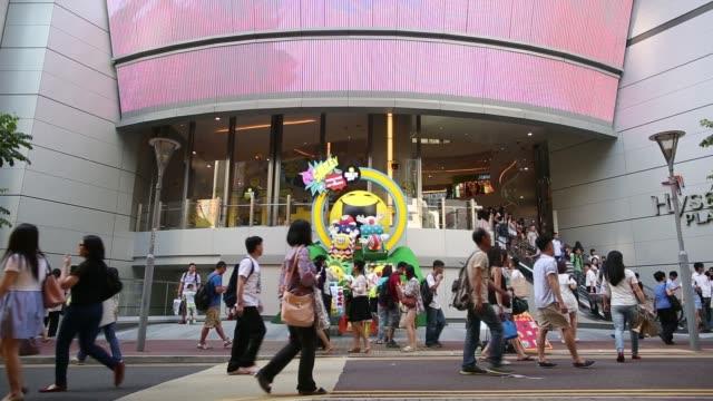 vídeos de stock, filmes e b-roll de shoppers ride an escalator past signage for hysan development cos hysan place mall at the malls entrance in the causeway bay district of hong kong... - ilha de hong kong