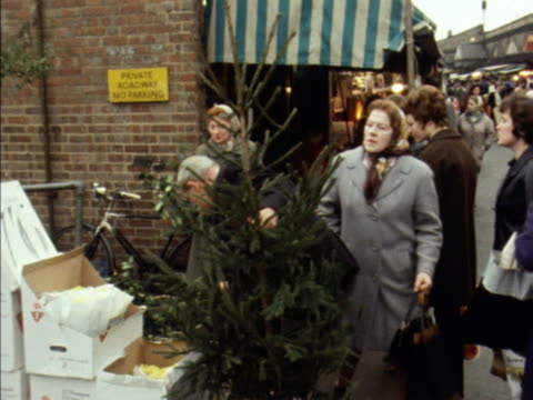 Shoppers select mistletoe and holly from a market stall
