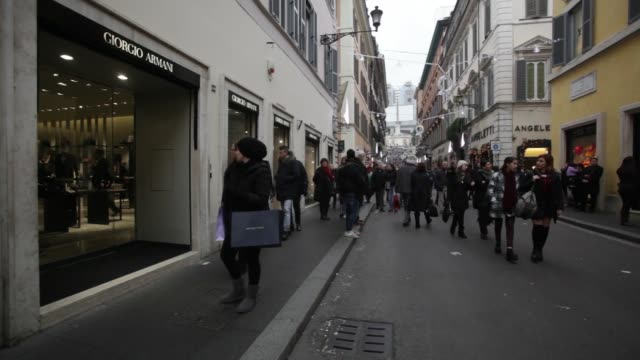 shoppers standing outside a store with branded shopping bags in rome italy on saturday january 3 pedestrians passing discount signs displayed inside... - cartier video stock e b–roll