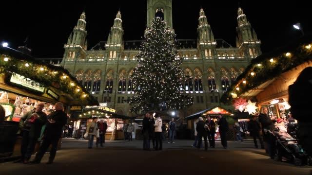 Shoppers stroll through an outdoor market in Vienna during the Christmas season.
