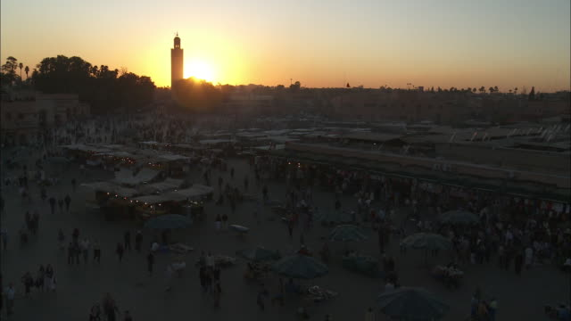 shoppers stroll through the marrakesh jemaa el fna market at the golden hour. - golden hour stock videos & royalty-free footage