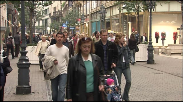 shoppers use a cobblestone sidewalk in a budapest retail district. - schieben stock-videos und b-roll-filmmaterial
