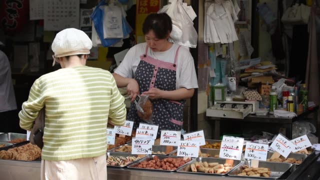 Shoppers walk along the Sunamachi Ginza shopping street in Tokyo Japan on Tuesday May 31 A customer shops at a cooked food store at the Sunamachi...