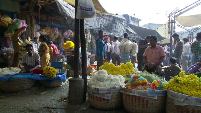 Shoppers walk among vendors at a flower market.