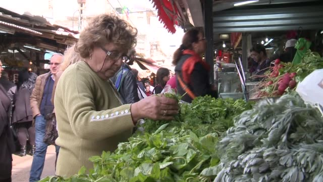Shoppers walk by vendors pick up parsley and other vegetables