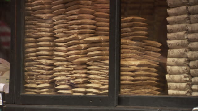 Shoppers walk past a shop window piled high with brown bags in Istanbul, Turkey.