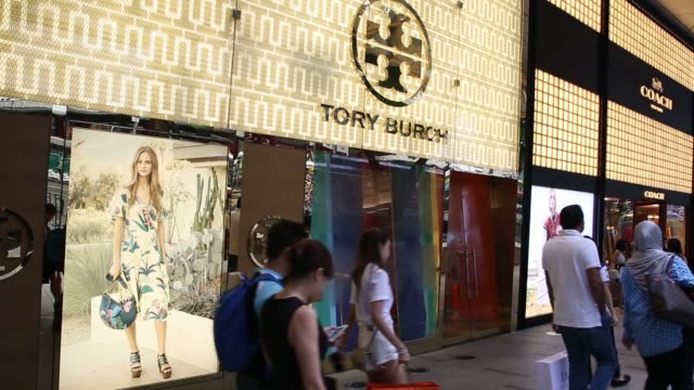 shoppers walk past a tiffany & co. store, left, and cartier luxury store, operated by cie. financiere richemont sa, right, on orchard road in... - cartier stock videos & royalty-free footage