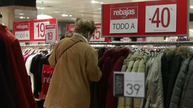 Shoppers walk past the El Cortes Ingles department store on the first day of sales in Madrid Spain on Tuesday Jan 7 A seventy per cent discount sign...