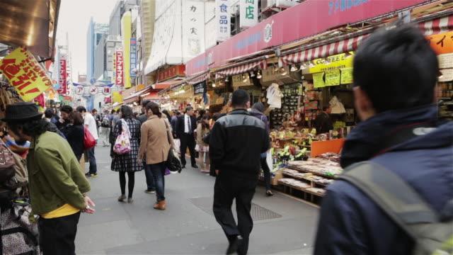 vídeos y material grabado en eventos de stock de ws shoppers walk through ameya yokocho market in ueno / tokyo, japan - lugar de comercio