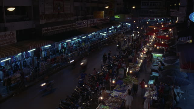 Shoppers walk through an outdoor marketplace at night as a group of motorcycles drive by.