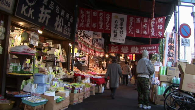 vidéos et rushes de shoppers walking past stalls at tsukiji fish market at night / tokyo - marché établissement commercial
