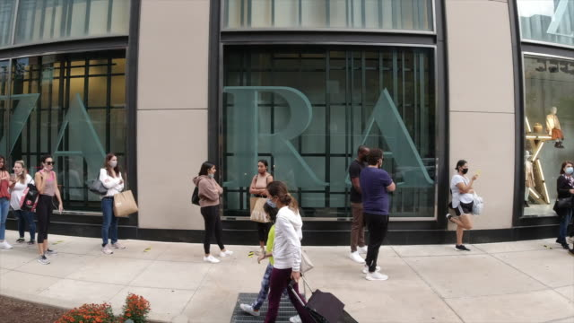 shoppers wearing face mask waiting outside the zara store in chicago. - illinois stock-videos und b-roll-filmmaterial