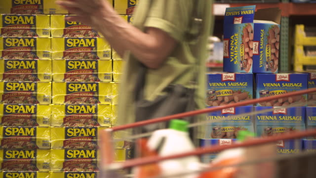 shoppers with a trolley walk past wholesale packets of spam and libby's vienna sausage at a costco warehouse usa fkax253n clip taken from programme... - 積み重なる点の映像素材/bロール