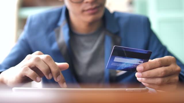 geschäftsmann mit tablet pc und halten eine kreditkarte einkaufen - elektronischer handel stock-videos und b-roll-filmmaterial