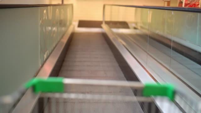 vídeos de stock, filmes e b-roll de o carrinho de compras está deslizando pela escada rolante. - mercado espaço de venda no varejo