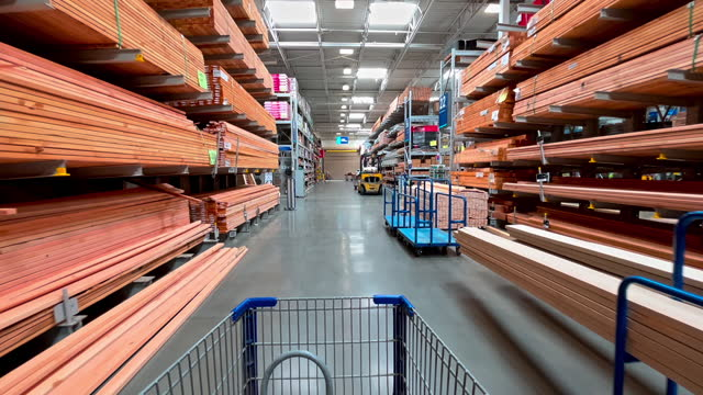 shopping cart moving down aisle of big box hardware store stocking lumber for construction on march 31,2021 in los angeles, california. - price tag stock videos & royalty-free footage