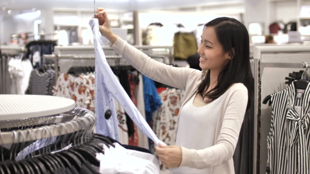 shopping clothes in shopping mall - clothes shop stock videos and b-roll footage