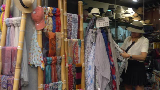vídeos de stock, filmes e b-roll de shopping for scarves in the village of orvieto, tuscany, italy, europe. - só uma mulher madura