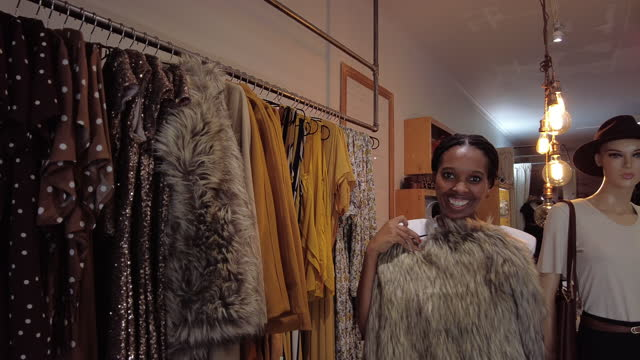 shopping in clothes store finding items on sale that she loves - shopaholic stock videos & royalty-free footage