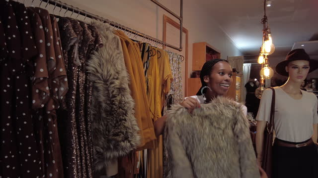 vídeos de stock e filmes b-roll de shopping in clothes store finding items on sale that she loves - shopaholic