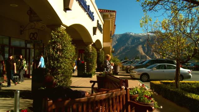 vídeos de stock e filmes b-roll de ms, shopping mall exterior with parking lot and mountains in background, cabazon, california, usa - shopping centre