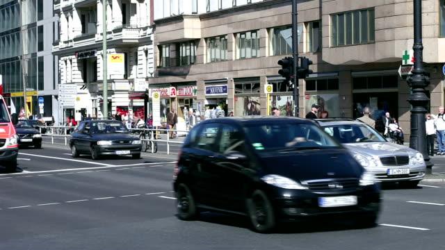 Einkaufsstraße mit vielen Menschen und Autos